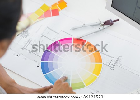 Interior designer looking at colour wheel at desk in creative office