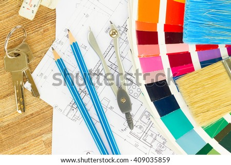 Interior designer's working desktop with  architectural plan of the house, keys, color palette and  brushes - stock photo