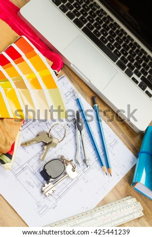 Interior designer's working desktop with  architectural plan of the house, keys, color palette and laptop  - stock photo