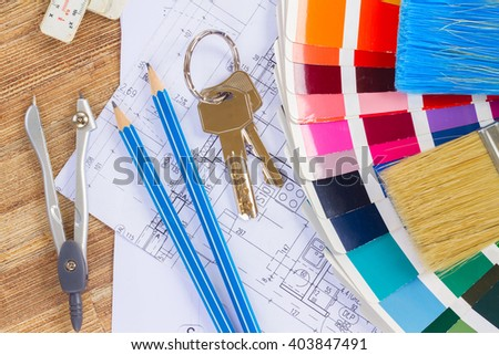Interior designer's working table with  architectural plan of the house, keys, color palette and  brushes - stock photo