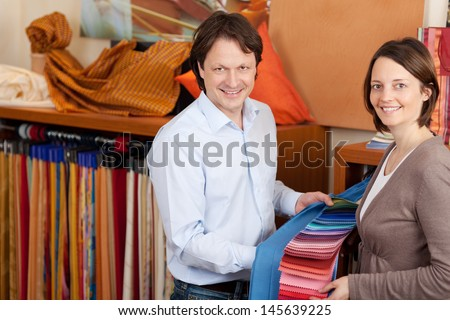 Interior designer talking to a client advising her on harmoniously matching color samples of fabrics - stock photo