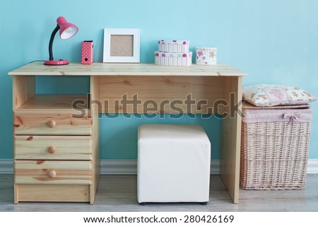 Interior detail. Study table and decor for kid girl in bedroom over blue wall