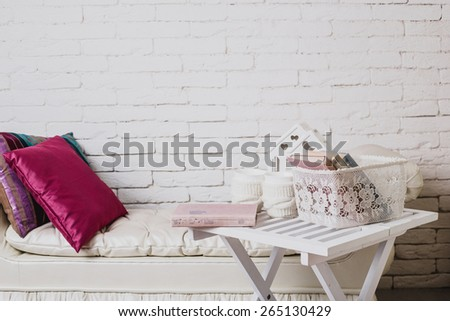 Interior details. White brick wall. Part of interior with couch and decorative pillows, white wooden table with books on it - stock photo