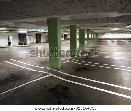 Interior from empty indoor carpark with oil stains on floor and green columns - stock photo