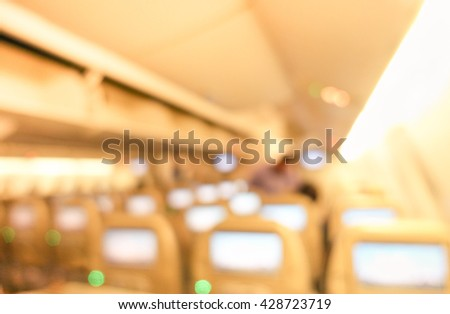 Interior international airplane flight - Defocused image - Abstract blur of sitting place with small screens - Soft warm brown filter - stock photo