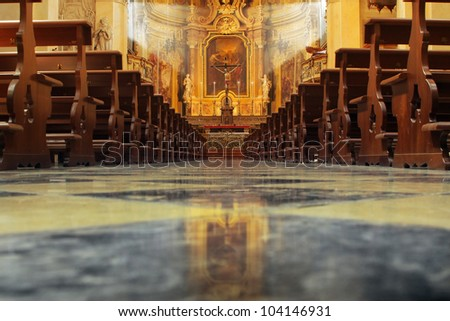 Interior of a beautiful old catholic church from below with marble floor, wooden pews, and light streaming onto altar with Jesus on crucifix - stock photo