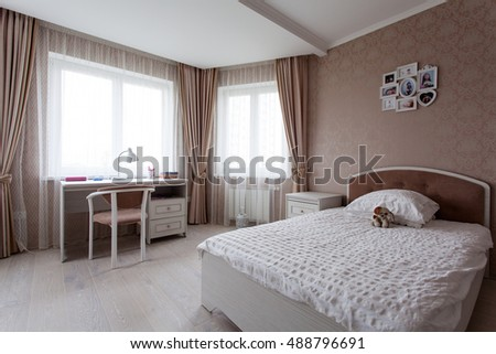 Interior of a bedroom with a large bed in light brown tones for little girl