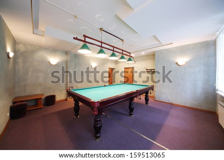 Interior of a billiard room with a pool table in the center - stock photo