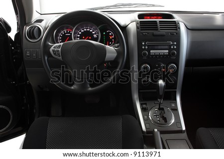 Interior of a car with view on steering wheel and dashboard - stock photo