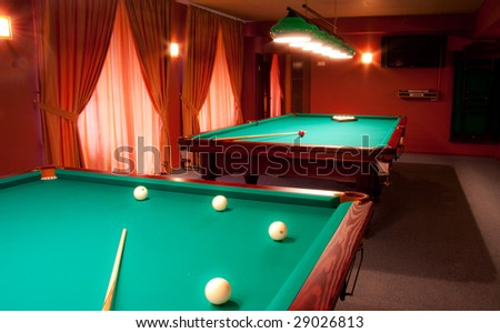 Interior of a club having billiard tables illuminated with lights - stock photo