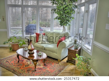 Interior of a corner room with tall windows and a view outside.
