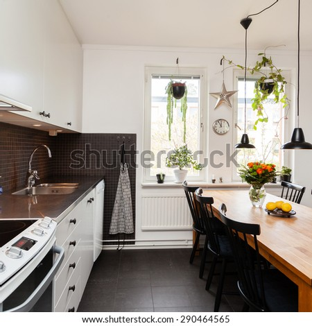 interior of a fancy kitchen with kitchen table and black floor - stock photo