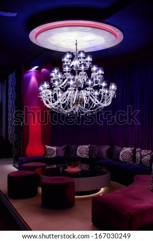 interior of a fancy nightclub with chandelier and sofas
