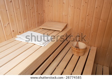 Interior of a finnish sauna with towel and bucket - stock photo