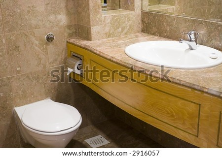 Interior of a hotel bathroom showing wash basin and toilet bowl