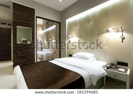 Interior of a hotel bedroom in the evening - stock photo