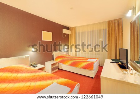 Interior of a hotel room for two, with furniture. Orange and brown colors as a main design details.