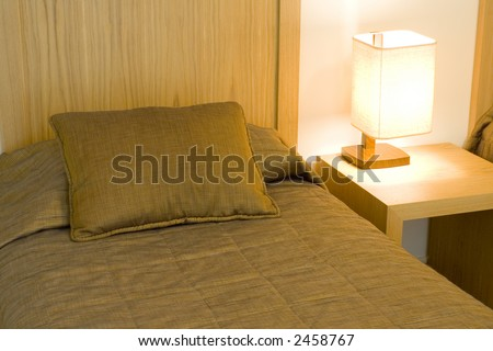 Interior of a hotel room showing the bed and side table - stock photo