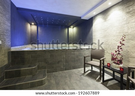 Interior of a hotel spa with jacuzzi bath with ambient led lights - stock photo