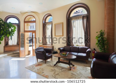 Interior of a hotel waiting room with a view on entrance doors. Day time, city life. - stock photo