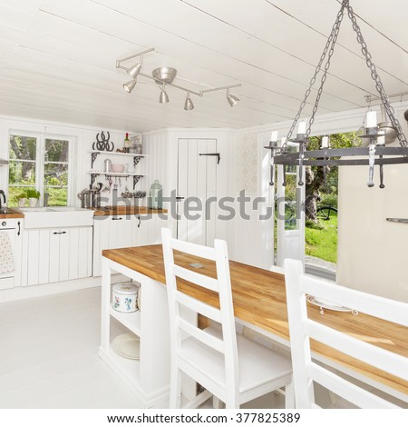 interior of a kitchen in the countryside with white wooden floor and ceiling - stock photo