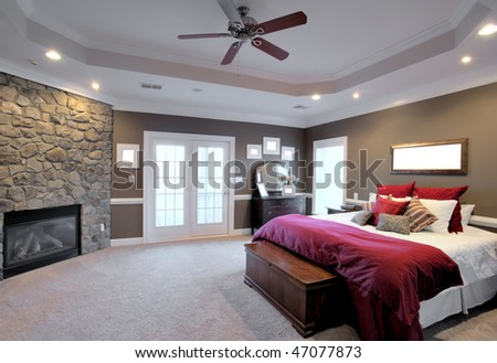 Interior of a large modern bedroom with a fireplace and ceiling fan. Horizontal format. - stock photo