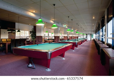 Interior of a large pool center, with neatly aligned pool tables