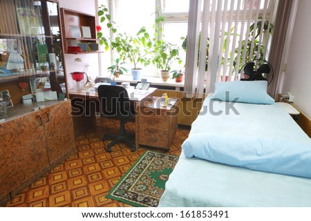 Interior of a light doctors consulting room with a bed and a workplace - stock photo
