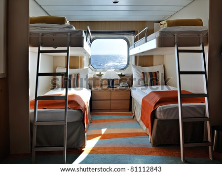 interior of a living cabin on a cruise ship - with bunk beds and window - stock photo
