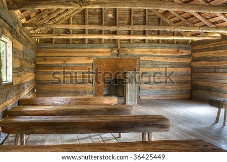 Interior of a log cabin vintage church in natural light with benches and pulpit. - stock photo