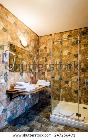 Interior of a modern bathroom. Shower cabin, basins, white towels. The vertical position photo. - stock photo
