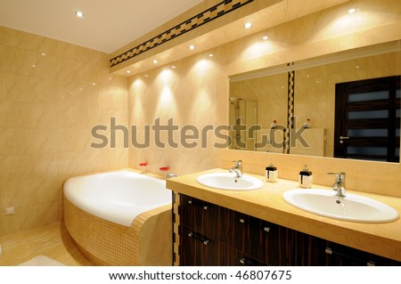Interior of a modern bathroom with a mirror, lights and red flowers on a tub. - stock photo