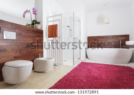 Interior of a modern bathroom with pink carpet and wooden wall - stock photo