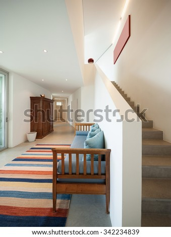 Interior of a modern house, hall with divan and striped rug - stock photo