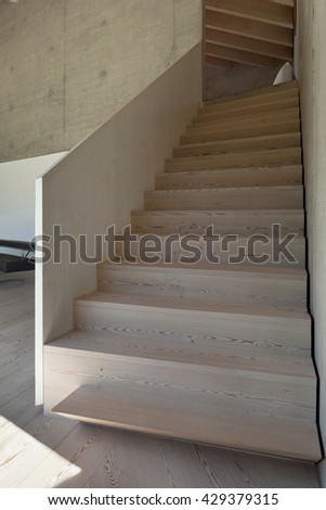 Interior of a modern loft in cement, wooden staircase