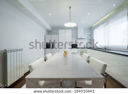 Interior of a modern luxury bright white kitchen with dining table - stock photo