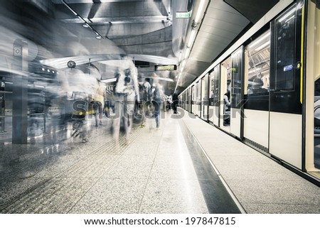 Interior of a modern subway station,  blurred people