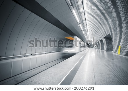 interior of a modern subway station, blurred train