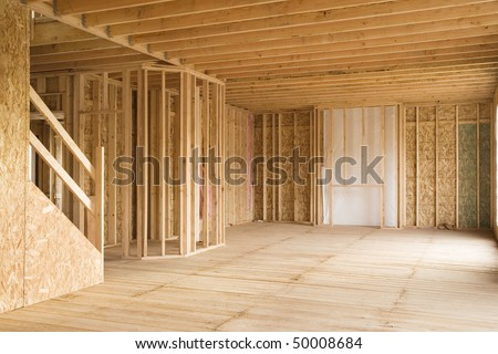 Interior of a new home under construction, with stairs to the left and an opening for a fireplace in the background. Horizontal shot. - stock photo