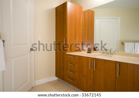 Interior of a new modern bathroom. Wooden cabinets, marble counter top, large mirror and chrome faucet.