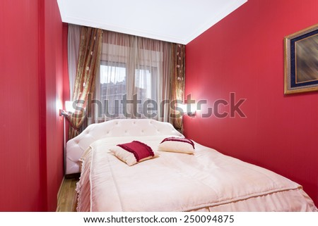 Interior of a red hotel bedroom - stock photo