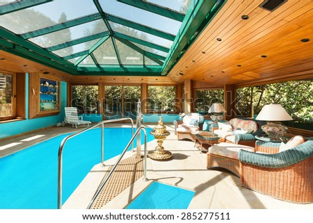 Interior of a residential house, large indoor pool, ceiling with skylights - stock photo
