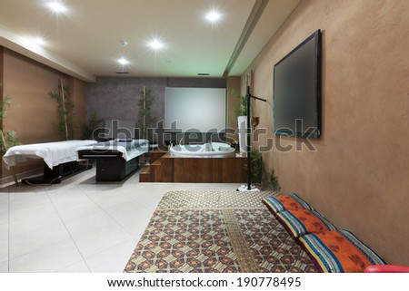 Interior of a room for relaxation treatment with jacuzzi bath and massage table - stock photo