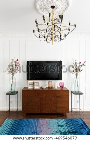 interior of a room with white walls, a TV and a dresser in a contemporary style