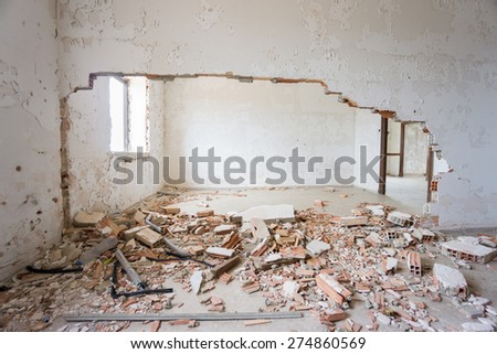 Interior of abandoned and ruined house with broken wall - stock photo
