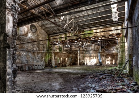 interior of abandoned factory with rubble and debris - desolate room of an old destroyed industrial warehouse - hdr image - stock photo