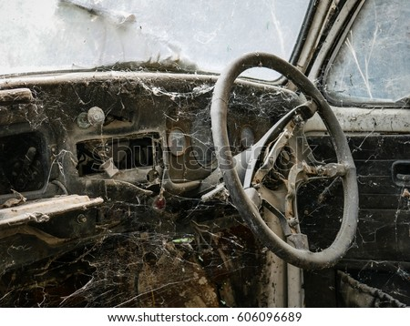 Interior of abandoned old car with spider web, damaged dashboard, creepy and  gloomy atmosphere, scary background