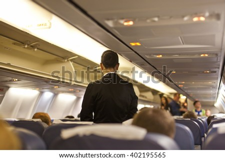Interior of airplane with passengers  and stewardess walking the aisle. - stock photo