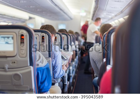 Interior of airplane with passengers during flight.  - stock photo
