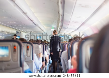 Interior of airplane with passengers on seats during flight. Stewardess in dark blue uniform walking the aisle. Horizontal composition. - stock photo